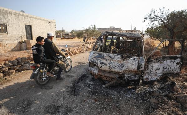 Syrians ride a motorcycle past a burnt vehicle near the northwest Syrian village of Barisha in the Idlib province of Syria, near where U.S. forces raided an ISIS compound.