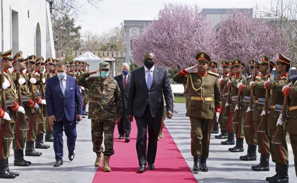 """U.S. Defense Secretary Lloyd Austin (center) reviews an honor guard at Afghanistan's presidential palace in Kabul on March 21. President Biden says all U.S. troops will leave Afghanistan by September, though the Americans will still assist from """"over the"""