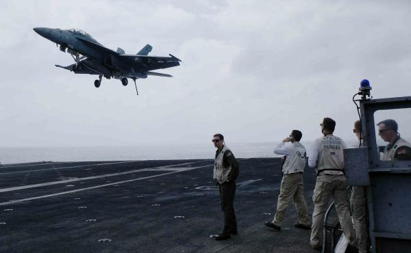 A Navy fighter jet comes in for a landing on the aircraft carrier USS Carl Vinson in the South China Sea.