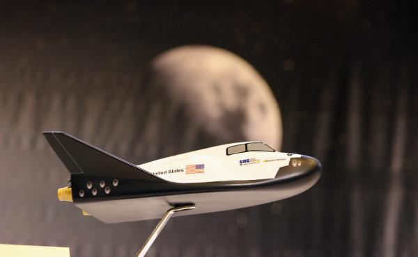 A model of the planned Dream Chaser mini-shuttle designed by Sierra Nevada Corp. is displayed in March 2014 for a news conference at NASA's Michoud Assembly Facility in New Orleans.