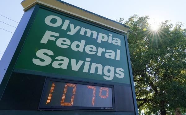A display at an Olympia Federal Savings branch shows a temperature of 107 degrees Fahrenheit on Monday in the early evening in Olympia, Wash.
