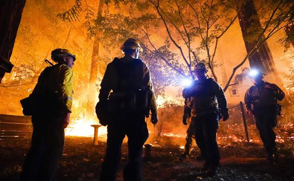 Firefighters make a stand in the backyard of a home in front of the advancing C.Z.U. Lightning Complex fire on Friday. California is seeing some of the worst first in the state's history.