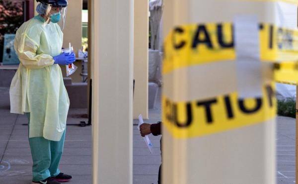 A doctor stands at a walk-up coronavirus testing site at West County Health Center in San Pablo, Calif., in April 2020. Pandemic burnout has affected thousands of health care workers.