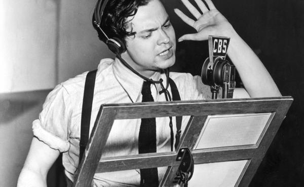 American actor, producer and director Orson Welles speaks into a microphone during a broadcast of his CBS radio program 'First Person Singular' circa 1938.
