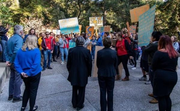 Graduate students marched on Kerr Hall, where the administration offices reside, to deliver their demands to the chancellor on Nov. 7. Watching in the foreground, with their backs to the camera, are Chancellor Cynthia Larive and Executive Vice Chancellor