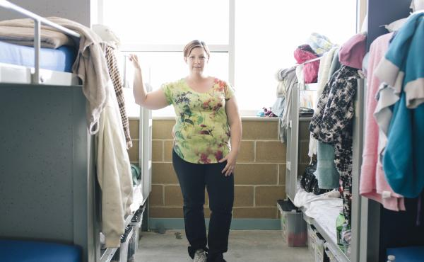 Jennifer Carter, 30, stands in a dormitory area that she shares with her two young children at The Road Home Community Winter Shelter facility in Midvale, Utah.