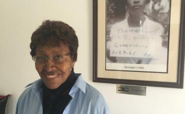 "Civil rights ""foot soldier"" Theresa Burroughs in 2016, in front of a photo of the day she was arrested in 1965. Burroughs has died at age 89."