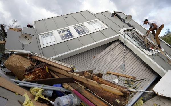 Jeremy Hodges climbs up the side of his family's destroyed storage unit on Monday, in Houma, La., which sits just along the coast of Louisiana.