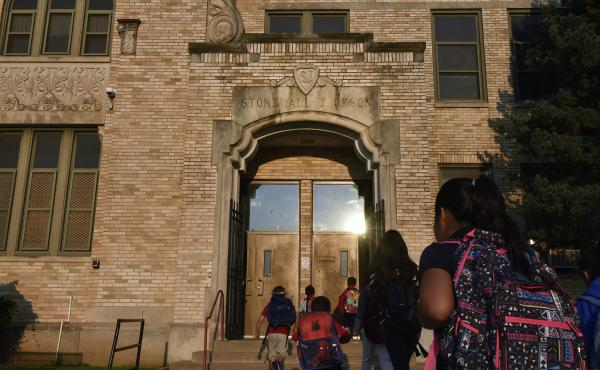 "Students walk through an entrance above which is engraved ""Stonewall Jackson"" at Jackson Elementary School in Oklahoma City."