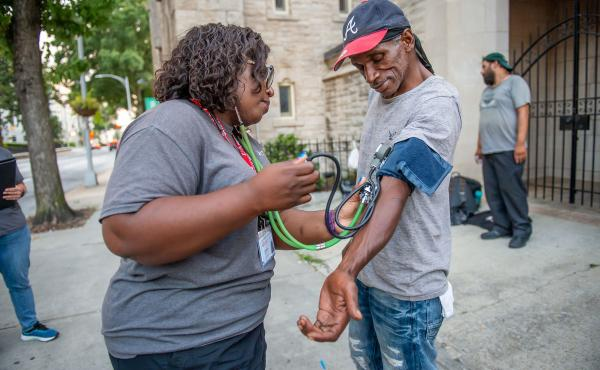 Licensed practical nurse Stephanie Dotson measures Kent Beasley's blood pressure in downtown Atlanta in September. Dotson is a member of the Mercy Care team that works to bring medical care to Atlanta residents who are homeless.