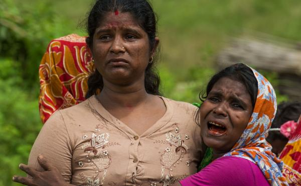 Hindu women cry at the site of a mass grave that Myanmar troops said they found last September in Maungdaw township. Amnesty International says local village leaders identified dozens of corpses unearthed from the graves the week before.