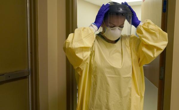A nurse puts on personal protective equipment as she prepares to treat a COVID-19 patient last month at a rural Missouri hospital.