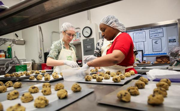 Elizabeth Bennett, director of partnerships, and Nikki Yates, program participant, place cookie dough they've just made onto baking sheets.