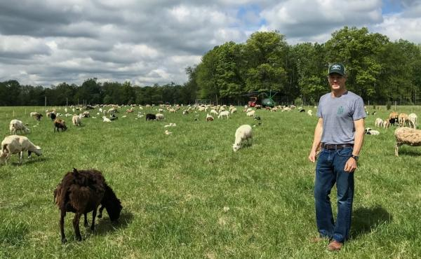 Jon McConaughy, owner of Double Brook Farms, stands in the field with his flock of sheep.