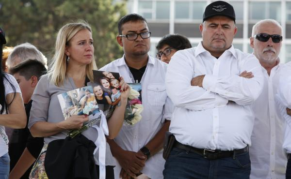 Adriana Jones, a member of the LeBaron family, holds images of relatives who were killed in November. Jones and other family members were participating in a Dec. 1 protest in Mexico City against Mexican President Andrés Manuel López Obrador to express a