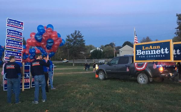 Volunteers from Republican Rep. Barbara Comstock's and Democratic challenger LuAnn Bennett's campaigns line up ahead of the Leesburg Halloween Parade in Loudon County, Va.