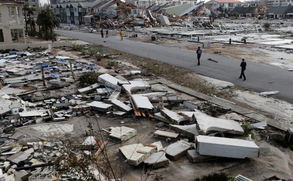 Rescue personnel walk through debris in Mexico Beach, which was devastated by Hurricane Michael.