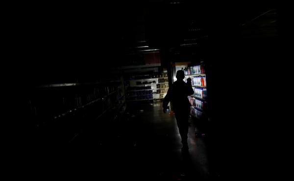 A worker inspects damage in a supermarket in Caracas on Sunday after it was looted during a days-long blackout in Venezuela.