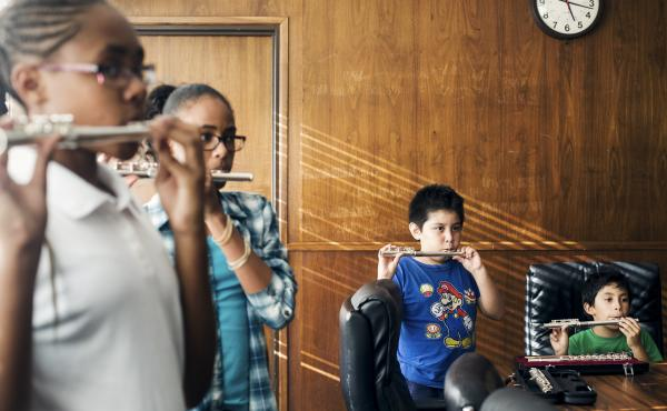 """A class for beginning flutists, crammed into an office building boardroom, labor over """"Hot Cross Buns."""" It's part of Harmony Project, a nonprofit program offering music lessons in a wide range of instruments — flute, trombone, trumpet, oboe, violin, cel"""