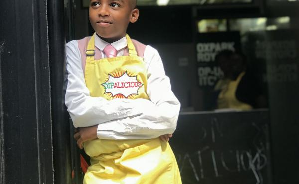 Chef Omari McQueen stands in the doorway of his vegan Caribbean pop-up restaurant Dipalicious.