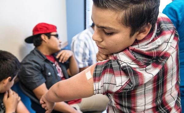 Abraham Vidaurre, 12, checks his arm after receiving an HPV vaccination at Amistad Community Health Center in Corpus Christi, Texas, in 2016. Though gender differences in vaccine rates have narrowed, more girls than boys tend to get immunized against HPV.