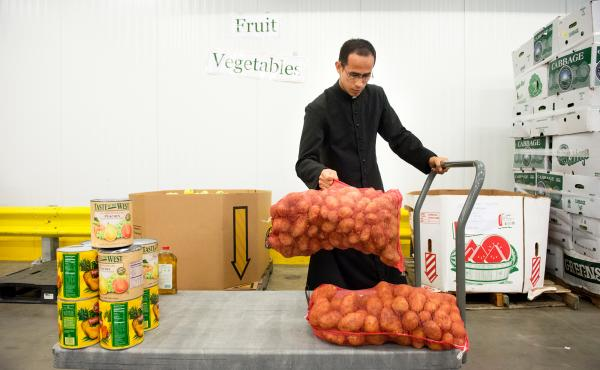 Brother William Valle of the Institute of the Incarnate Word in Chillum, Md., loads potatoes onto his cart at the Capitol Area Food Bank, in Washington, D.C. A new government initiative seeks to engage faith-based groups on food waste — for instance, by