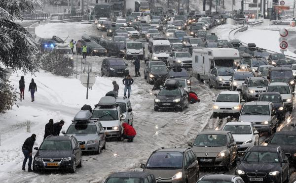 Drivers park to put on snow chains in the middle of a massive traffic jam in the Savoie region of France. Thousands of motorists are stranded for a second day.