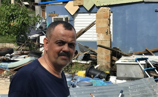 Roberto Fret, 54, stands in the backyard of his damaged home. Hurricane Maria blew the roof off the house; the wind was so powerful that it twisted the metal roofing material and scattered pieces of it all over the yard.