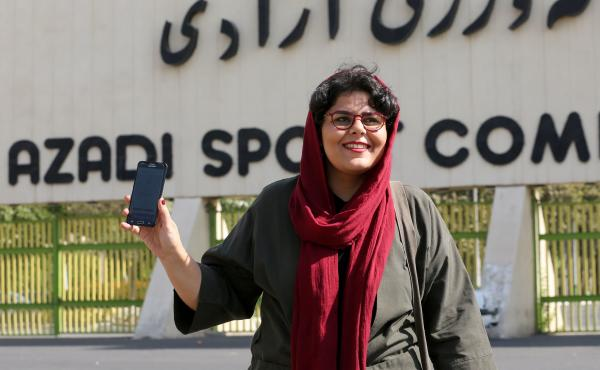 Iranian sports journalist Raha Purbakhsh shows off her ticket to attend a World Cup qualifier in front of Azadi Stadium in Tehran on Tuesday. Iran has essentially banned women from entering the stadium for decades.