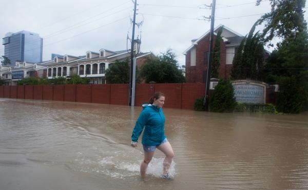 Kelli Walker wasn't able to get into her family's home, on the other side of the brick wall, because of the depth of the rising floodwater in Houston on Tuesday.