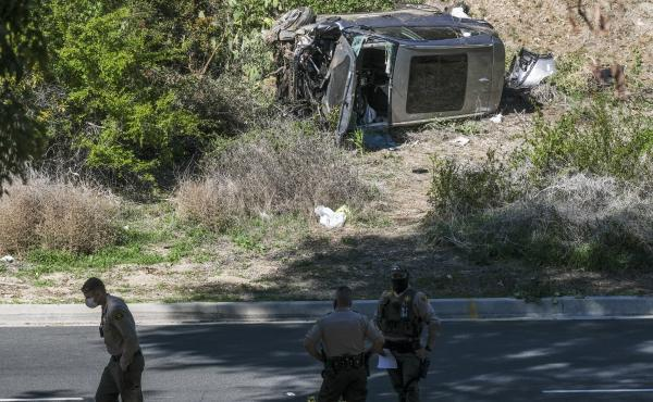A vehicle rests on its side after a rollover accident involving golfer Tiger Woods along a road in the Rancho Palos Verdes section of Los Angeles County on Tuesday. Woods suffered leg injuries in the one-car accident and was undergoing surgery, authoritie