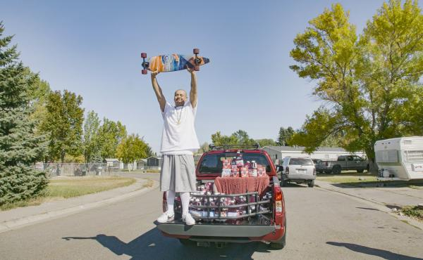 """Nathan Apodaca's TikTok video, in which he longboards to Fleetwood Mac's """"Dreams,"""" has catapulted him to viral fame. Here, he is standing in the pickup truck given to him by Ocean Spray. In his video, Apodaca sips from a bottle of Ocean Spray's Cran-Raspb"""