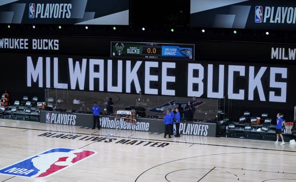 Officials stand beside an empty court at the scheduled start of an NBA basketball playoff game between the Milwaukee Bucks and the Orlando Magic, Wednesday in Lake Buena Vista, Fla. The Bucks didn't take the floor in protest against racial injustice and t