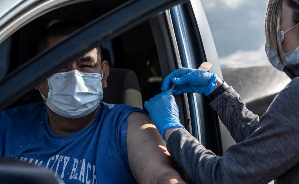 A medical professional from UofL Health administers a vaccine to a patient in their vehicle at University of Louisville Cardinal Stadium.