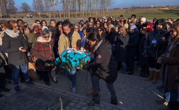 Members of a group of French women from diverse religious and ethnic backgrounds lay a wreath near the Auschwitz gas chambers earlier this month. After learning more about the horrors of the Holocaust, they hoped to bring greater understanding to their co