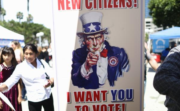 A sign encourages newly sworn-in U.S. citizens to register to vote outside a naturalization ceremony in 2019 in Los Angeles. After failing to get the now-blocked citizenship question on the 2020 census, the Trump administration is continuing to gather gov