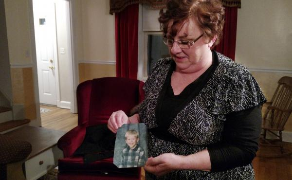 """Toni Hoy, at her home in Rantoul, Ill., holds a childhood photo of her son, Daniel, who is now 24. In a last-ditch effort to get Daniel treatment for his severe mental illness in 2007, the Hoys surrendered parental custody to the state. """"When I think of h"""