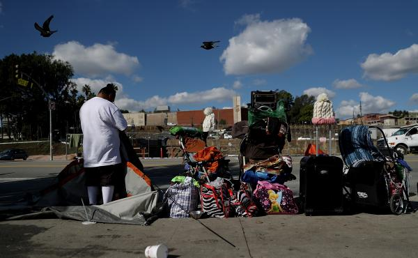 A homeless woman packs up her tent last January in Los Angeles. In 2018, LA County has about 53,000 homeless people — more than any other major metropolitan area in the country besides New York City.