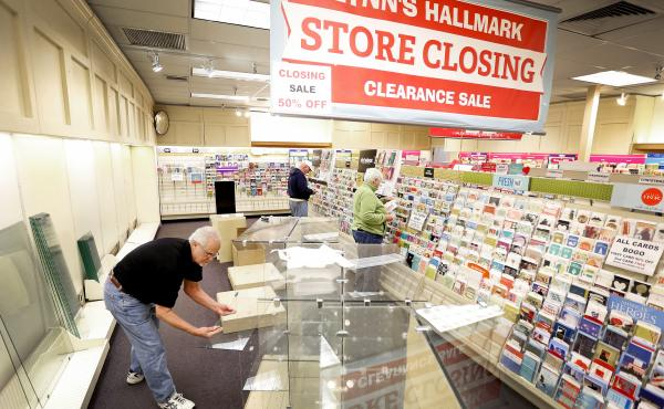 Owner David DeLongy takes apart glass shelving at Lynn's Hallmark store in Gainesville, Fla., which closed in February.