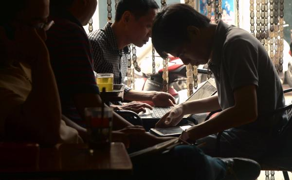 Men use tablets and laptops to check news at a coffee shop in Hanoi in 2014. Today almost half of Vietnam's population of over 95 million have access to the Internet. A new and controversial cybersecurity law goes into effect nationwide Tuesday.