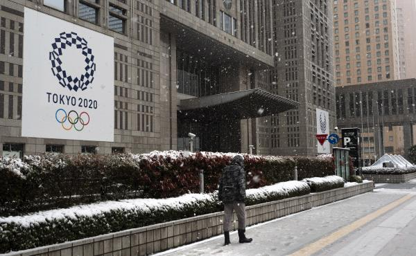 The International Olympic Committee has set firm dates for the delayed Tokyo 2020 Olympics, which are now set to start in July 2021. Here, a man walks past a banner promoting the Tokyo 2020 Olympics on Sunday, after a late-season snow in Tokyo.