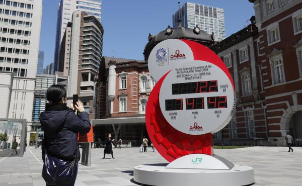 A person in Tokyo takes a photo of a clock counting down the days until the planned start of the Tokyo Games. They will now take place next year.