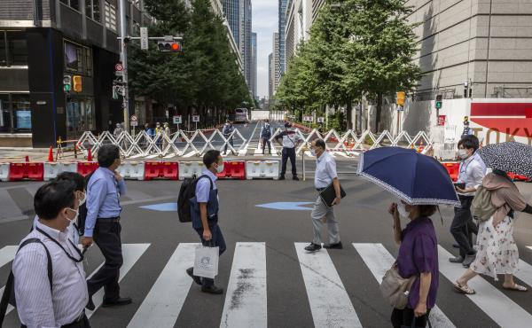 Tokyo's government is reporting new daily coronavirus cases at a rate not seen in more than six months. Here, people cross a street next to the Tokyo International Forum.