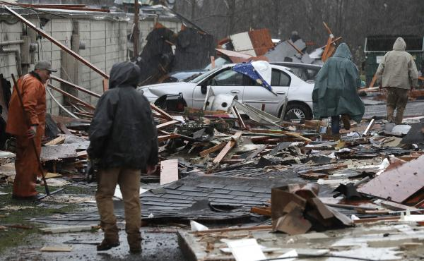 People walk through debris at Salmonberry Dry Storage in Port Orchard, Wash., where a rare tornado touched down Tuesday.