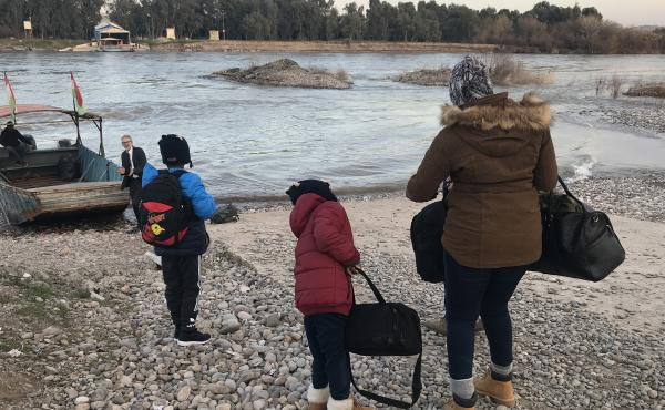 Mahmud, 11, Ayyub, 7, and their mother, Felicia Perkins-Ferreira, walk toward the boat that will take them out of Syria, across the river to Iraq, so they can start their journey home to Trinidad.