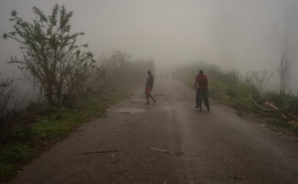 People are seen emerging from a mist on Sunday in eastern Zimbabwe. Cyclone Idai barreled across Mozambique, Malawi and Zimbabwe with flash floods and ferocious winds, killing people and destroying homes.