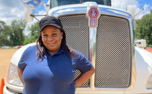 Pamela Williams, a driving instructor with DSC Training Academy, stands in front of one of the academy's trucks on June 29. Williams has been driving for seven years and enjoys seeing the country from the road.