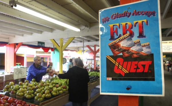 A sign announces the acceptance of electronic benefit transfer cards at a farmers market in California. Anti-poverty groups fear that many low-income people might be pushed off programs such as food stamps under a possible change to how the government mea
