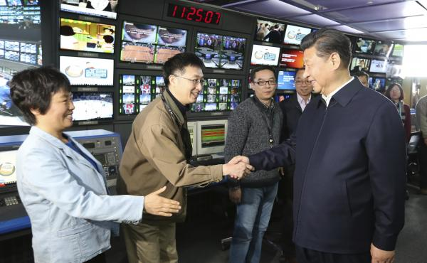 Chinese leader Xi Jinping (right) shakes hands with staff members at the control room of China Central Television in Beijing in 2016.