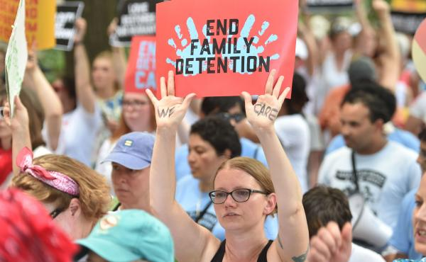 "People demonstrate in Washington, D.C., on Thursday, demanding an end to the separation of migrant children from their parents. On Friday, the Justice Department said in a court filing that ""the government will not separate families but detain families to"